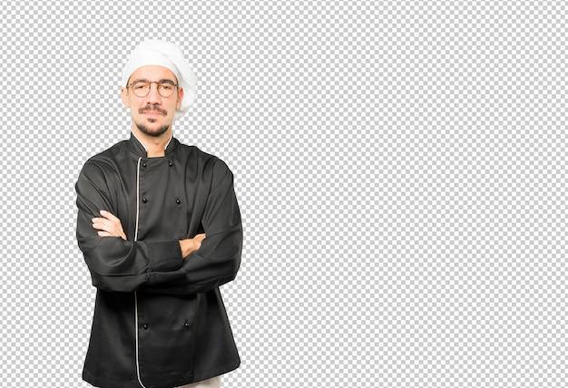 Joven chef satisfecho con gesto de brazos cruzados