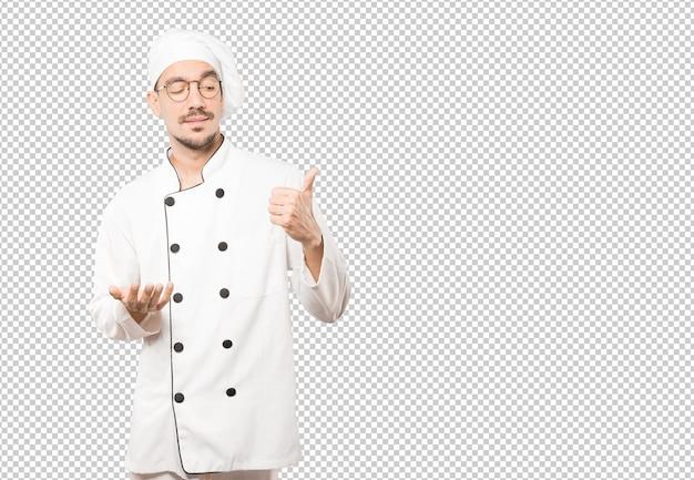 Joven chef vacilante gesticulando que todo está bien