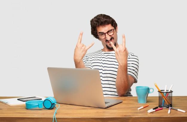 Joven diseñador gráfico barbudo con una computadora portátil cantando rock, bailando, gritando