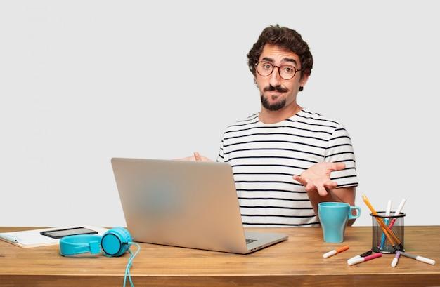 Joven diseñador gráfico barbudo con una computadora portátil con una mirada burlona y confusa