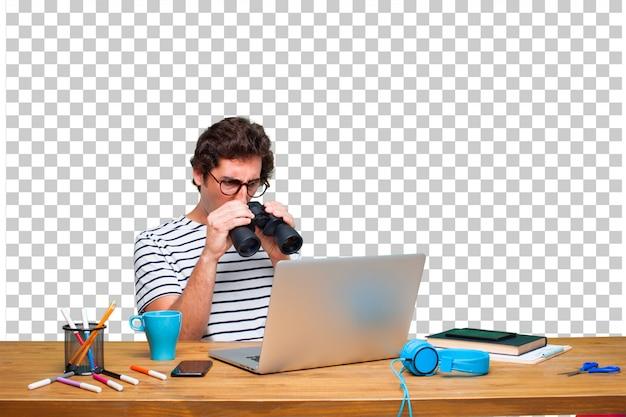 Joven diseñador gráfico loco en un escritorio con una computadora portátil y con binoculares