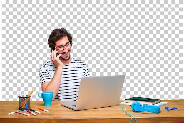 Joven diseñador gráfico loco en un escritorio con una computadora portátil y con un teléfono con pantalla táctil inteligente