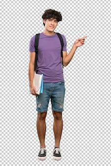 Joven estudiante hombre apuntando con el dedo al lado