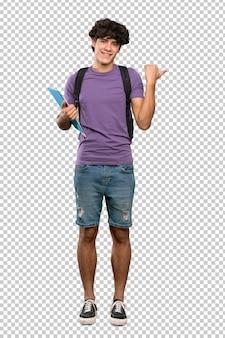 Joven estudiante hombre apuntando hacia un lado para presentar un producto