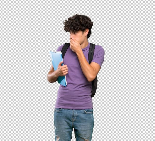 Joven estudiante hombre cubriendo la boca y mirando hacia un lado