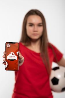 Joven futbolista mostrando maqueta de dispositivo digital