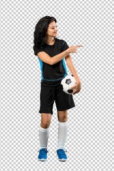 Joven futbolista mujer apuntando hacia un lado para presentar un producto