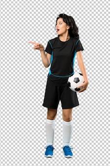 Joven futbolista mujer sorprendida y apuntando con el dedo al lado