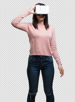 Joven y guapa mujer emocionada y entretenida, jugando con gafas de realidad virtual, explorando un mundo de fantasía, tratando de tocar algo