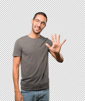 Joven haciendo un gesto número cinco