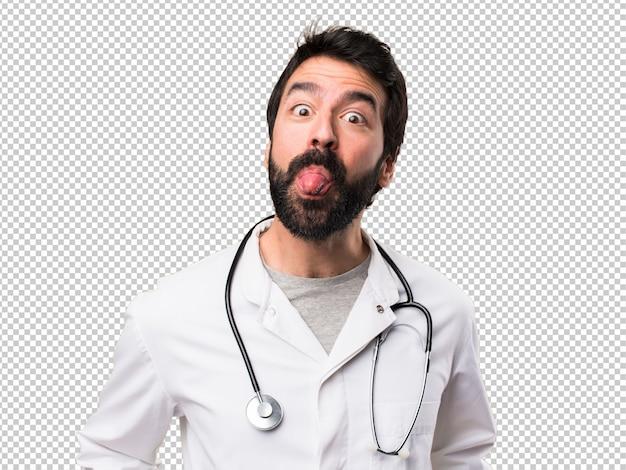 Joven médico sacando la lengua