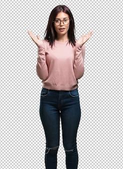 Joven mujer bonita sorprendida y conmocionada, mirando con los ojos muy abiertos, entusiasmada por una oferta o por un nuevo trabajo, gana el concepto