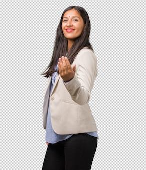 Joven mujer india de negocios invitando a venir, confiada y sonriente haciendo un gesto con la mano, siendo positiva y amigable