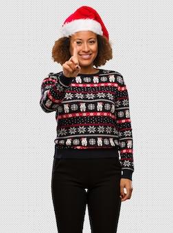 Joven mujer negra en un suéter navideño de moda con estampado que muestra el número uno