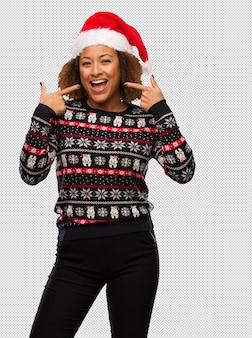 Joven mujer negra en un suéter navideño de moda con sonrisas estampadas, señalando la boca