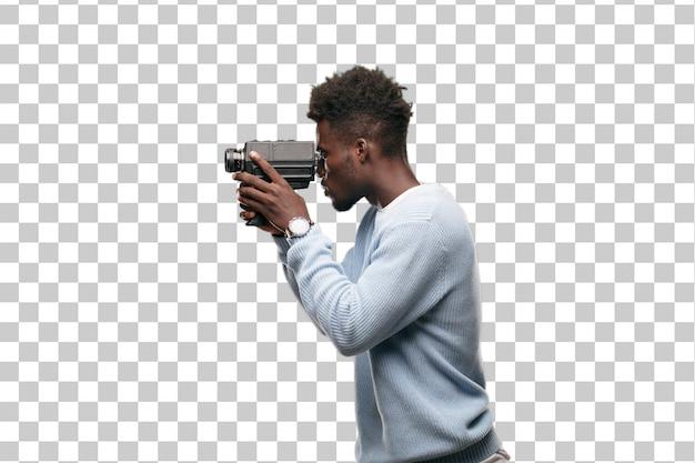 Joven negro grabando con una cámara de cine super 8 vintage.