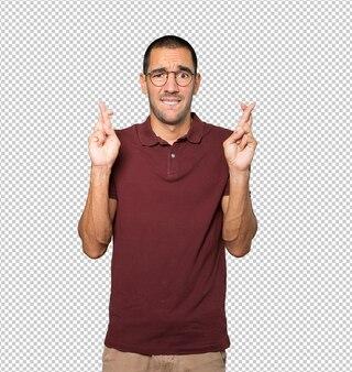 Joven preocupado haciendo un gesto de dedos cruzados