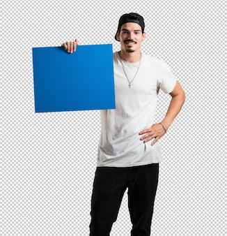 Joven rapero alegre y motivado, mostrando un cartel vacío donde puedes mostrar un desastre.