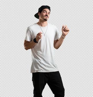 Joven rapero escuchando música, bailando y divirtiéndose, moviéndose