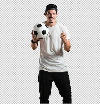 Joven rapero hombre sonriente y feliz, sosteniendo un balón de fútbol, actitud competitiva, emocionado de jugar un juego