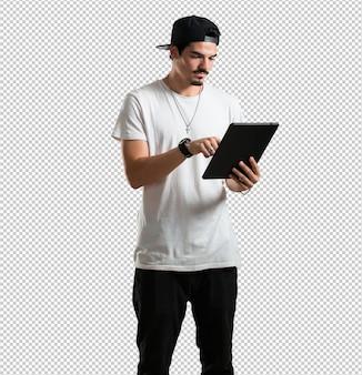 Joven rapero sonriente y confiado, sosteniendo una tableta, usándola para navegar por internet y ver las redes sociales
