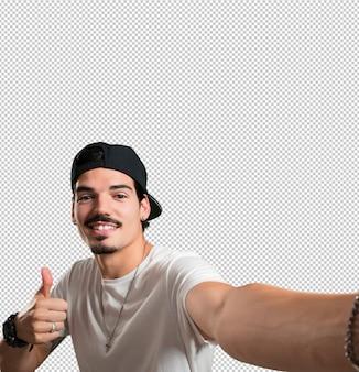 Joven rapero sonriente y feliz, tomando un selfie, sosteniendo la cámara
