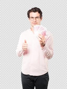 Joven rico con dinero con las manos