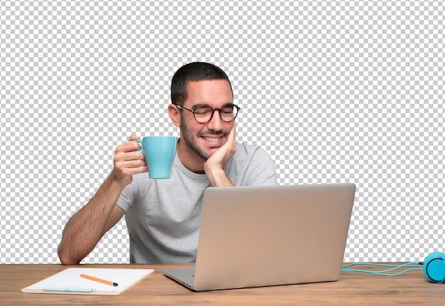 Joven sentado en su escritorio y tomando café
