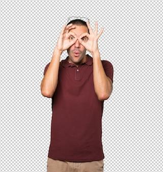 Joven sorprendido usando sus manos como binoculares