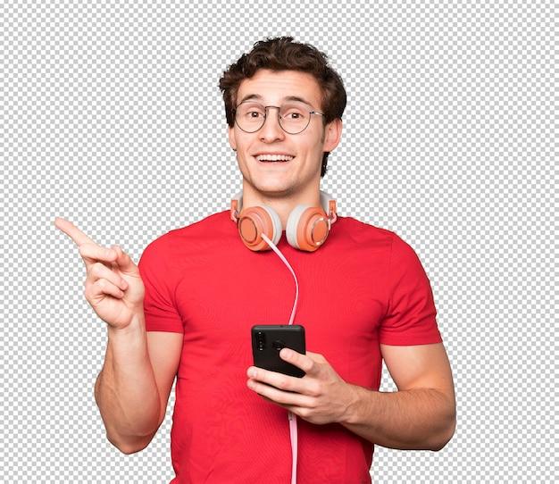 Joven sorprendido usando un teléfono inteligente y apuntando con su dedo