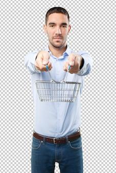 Joven sujetando una cesta de la compra