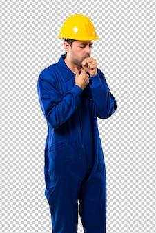 Joven trabajador con casco sufre con tos y se siente mal.