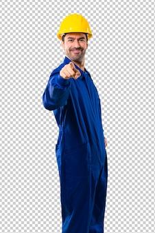 Joven trabajador con casco te señala con un dedo con una expresión de confianza