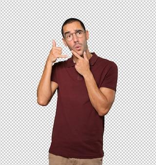Joven vacilante haciendo un gesto de llamar con la mano