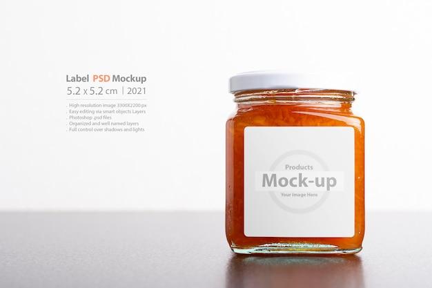 Jugosa mermelada de zanahoria casera en frasco de vidrio sobre un fondo blanco, serie de maquetas psd editables con plantilla de capas de objetos inteligentes lista para su diseño