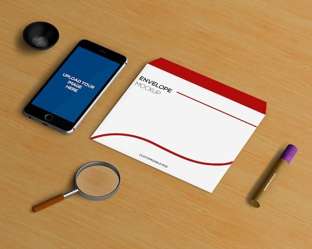 Kantoorbehoeftenconcept met envelop en smartphonemodel