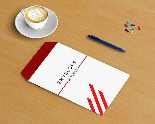 Kantoorbehoeftenconcept met envelopmodel en koffie