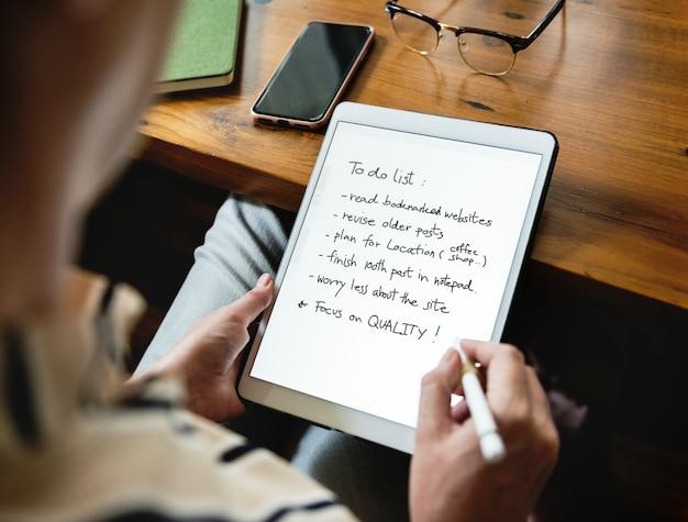 Kaukasische vrouw die lijst op tablet schrijft te doen Premium Psd
