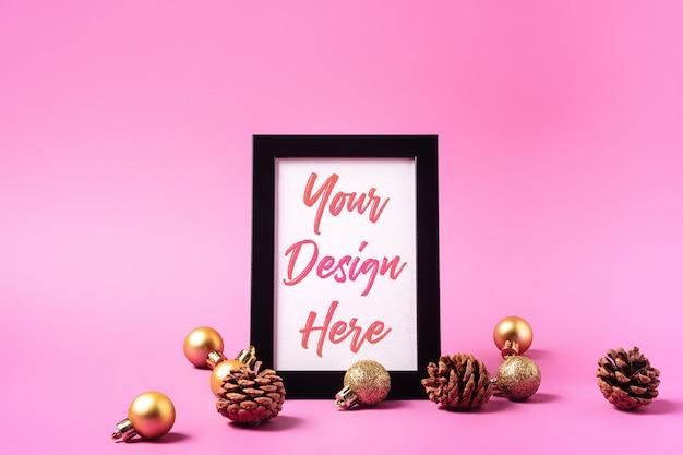 Kerst minimale compositie met leeg afbeeldingsframe. gouden ornament, dennenappels decoraties. mock up wenskaartsjabloon