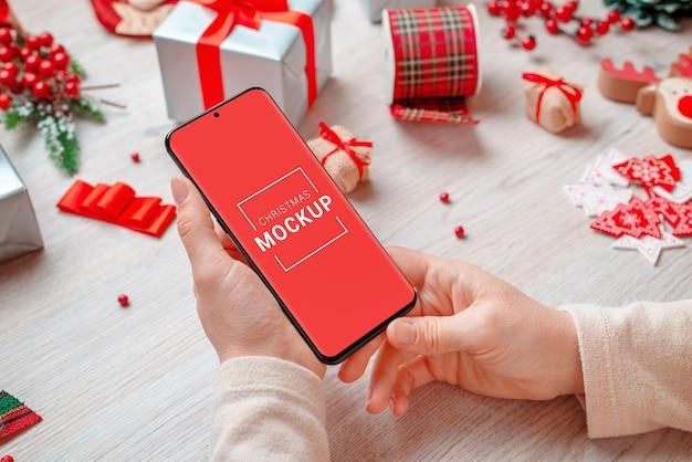 Kerst mobiele telefoon mockup in handen van de vrouw