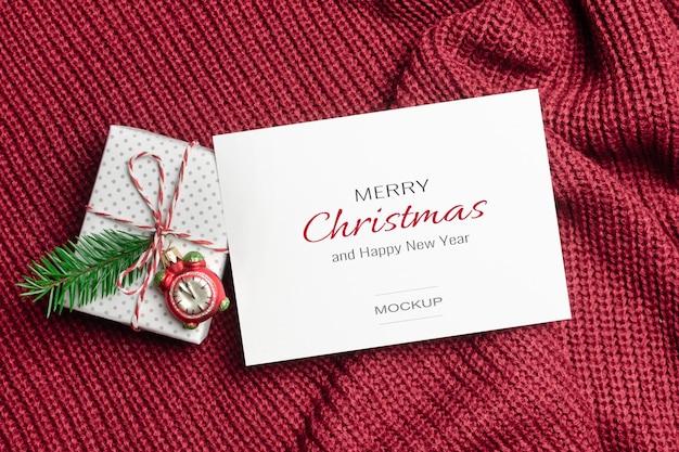Kerst of nieuwjaar wenskaart mockup met versierde geschenkdoos op gebreide achtergrond