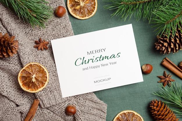 Kerst- of nieuwjaarswenskaartmodel met droge sinaasappels, kruiden en pijnboomtakken met kegels
