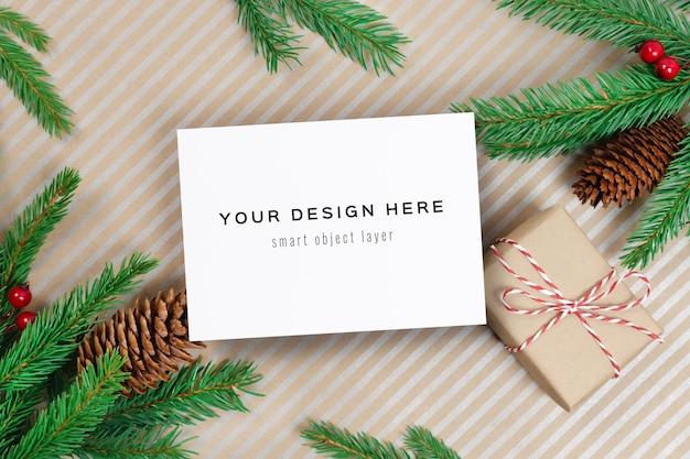 Kerst- of nieuwjaarswenskaartmodel met geschenkdoos en dennentakken met kegels