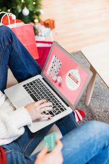 Kerst verkoop mockup met vrouw met behulp van laptop
