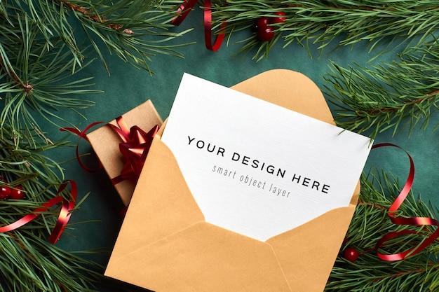 Kerst wenskaart in envelop mockup met geschenkdoos en pijnboomtakken op groen