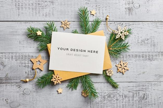 Kerst wenskaart mockup met dennentakken en houten decoraties