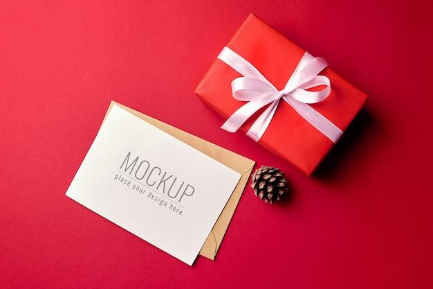 Kerst wenskaart mockup met geschenkdoos en dennenappel