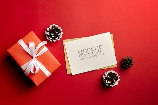 Kerst wenskaart mockup met geschenkdoos en dennenappels