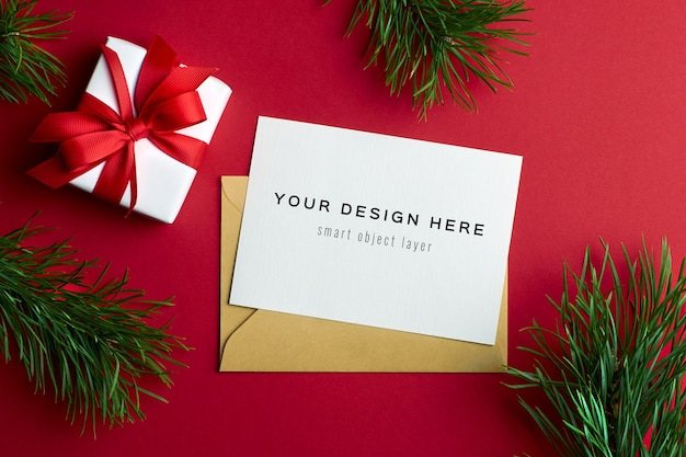 Kerst wenskaart mockup met geschenkdoos en pijnboomtakken op rood