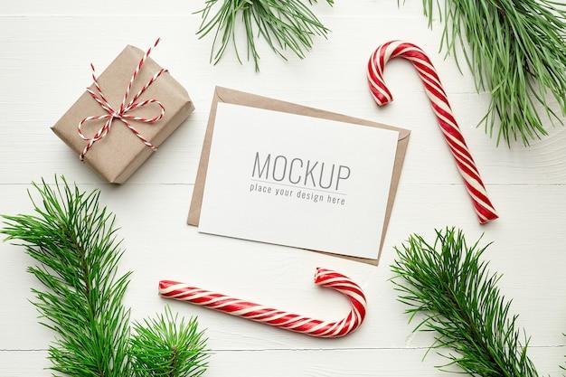 Kerst wenskaart mockup met geschenkdozen, zuurstok en pijnboomtakken